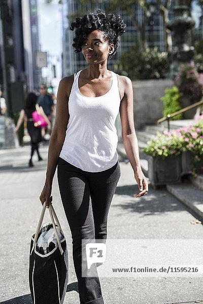USA  New York City  Manhattan  lächelnde Frau mit Einkaufstasche