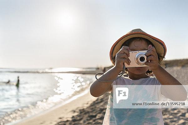 Spanien  Menorca  kleines Mädchen beim Fotografieren am Strand