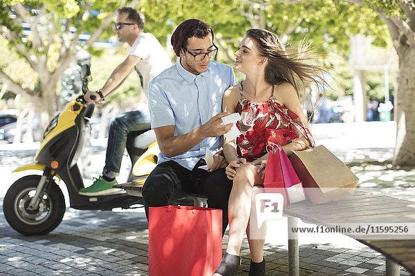 Mann überprüft Einkaufsrechnung mit Freundin  die ihn ansieht.