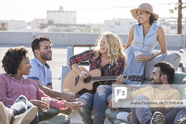 Freunde bei einer Dachparty und Gitarre spielen
