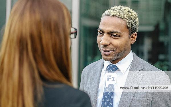 Junge Geschäftsleute im Gespräch vor dem Bürogebäude