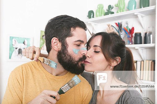 Young couple kissing holding paintbrushes