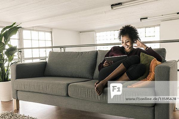 Lächelnde junge Frau auf der Couch sitzend mit Tablette