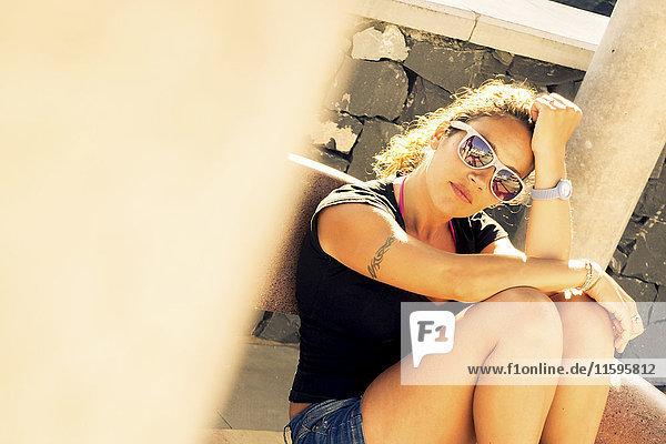 Frau mit Sonnenbrille  die auf einer Bank ruht