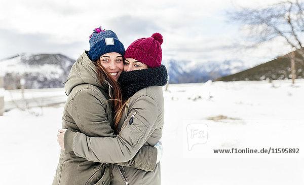 Zwei junge Frauen  die sich im Schnee umarmen.