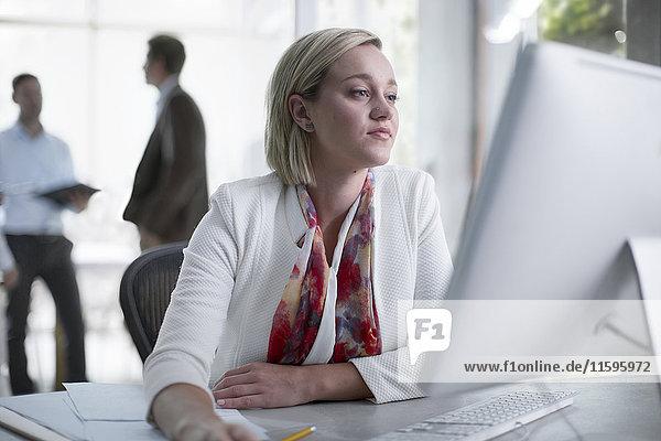 Mittlere erwachsene Geschäftsfrau  die im Büro arbeitet