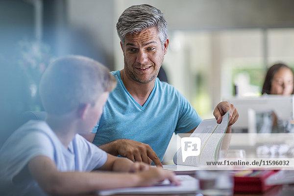 Vater hilft Sohn bei den Hausaufgaben Vater hilft Sohn bei den Hausaufgaben