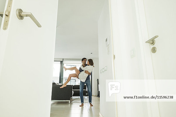 Verspielter junger Mann mit Freundin zu Hause