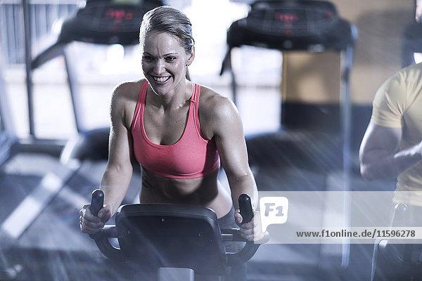 Lächelnde Frau auf dem Spinnrad im Fitnessstudio