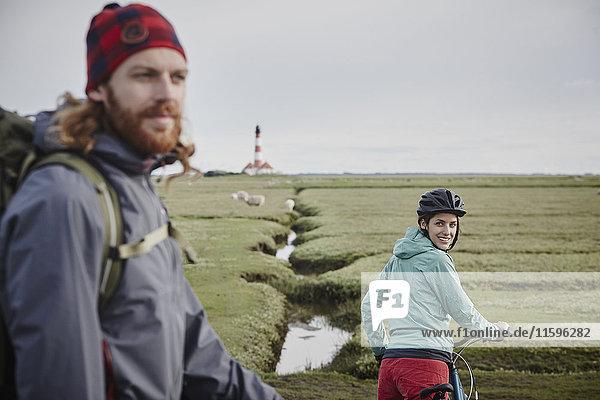 Deutschland  Schleswig-Holstein  Eiderstedt  Paar auf Fahrradtour bei Westerheversand Leuchtturm
