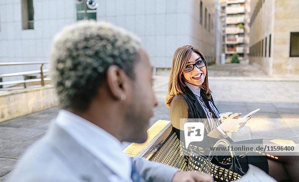 Ein junger Geschäftsmann und eine junge Frau  die auf einer Bank sitzen und reden.