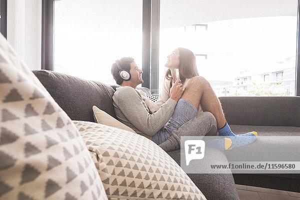 Glückliches junges Paar mit Kopfhörer und Smartphone auf der Couch