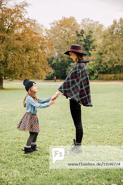 Junge Frau und kleines Mädchen stehen sich im Herbst auf einer Wiese gegenüber und halten sich an den Händen.