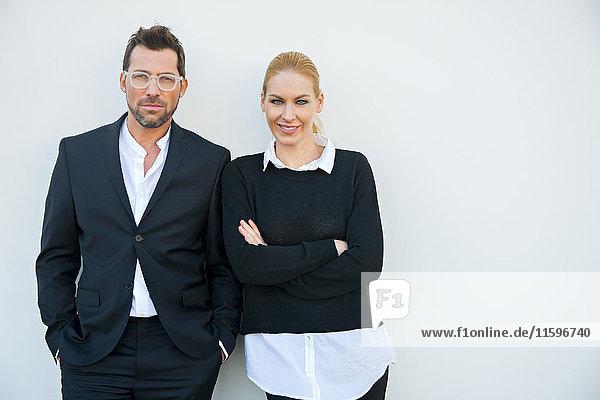 Porträt eines selbstbewussten Geschäftsmannes und einer Frau an der weißen Wand