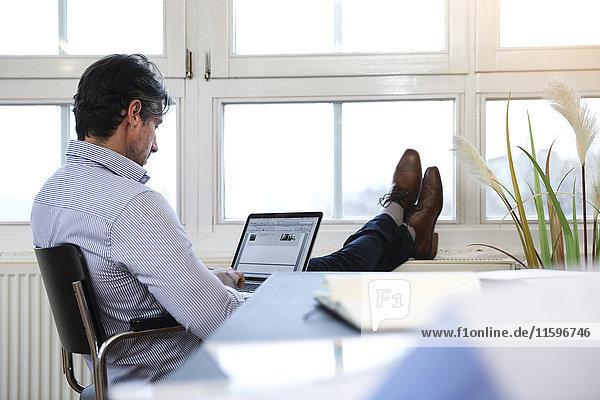 Mann mit Laptop am Fenster im Büro