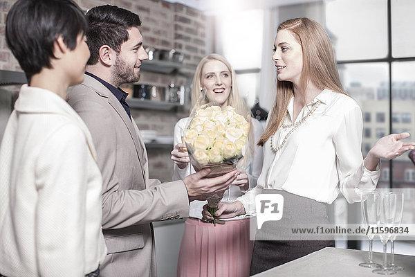 Mann übergibt Rosen an Frau in der Küche