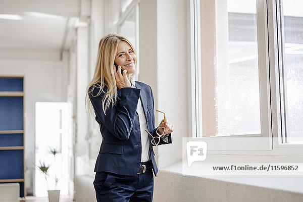 Porträt einer lächelnden Geschäftsfrau am Handy im Büro