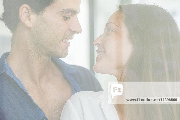 Lächelndes junges verliebtes Paar hinter der Fensterscheibe