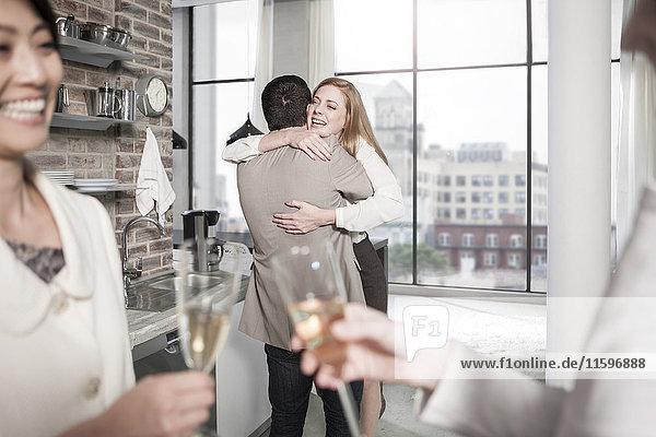 Mann und Frau umarmen sich in der Küche bei einer Versammlung
