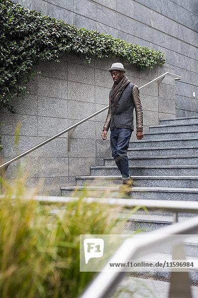 Junger Mann  der die Treppe hinuntergeht.