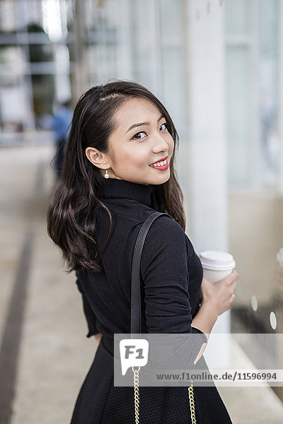 Portrait of smiling young woman with coffee to go looking over her shoulder