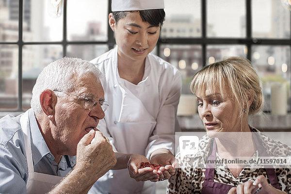 Seniorenpaar beim Verkosten von Samen im Kochkurs