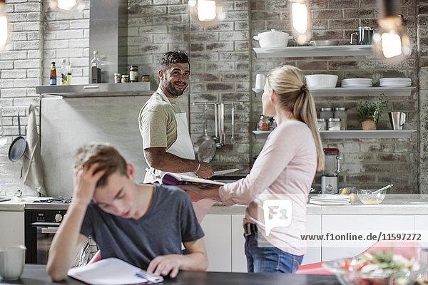 Familie zu Hause mit Sohn lernen und Vater kochen