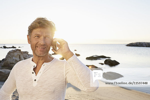 Portrait of smiling man using cell phone on the beach