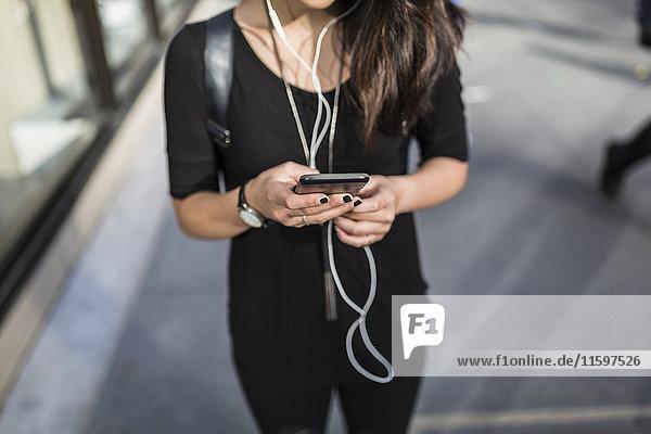 Junge Frau beim Musikhören mit Kopfhörern beim SMS-Versand  Teilansicht