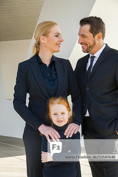 Lächelnder Geschäftsmann und Geschäftsfrau mit Mädchen