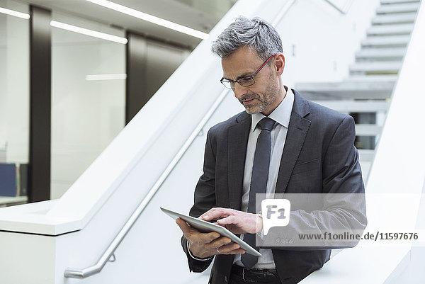 Porträt eines reifen Geschäftsmannes mit digitalem Tablett