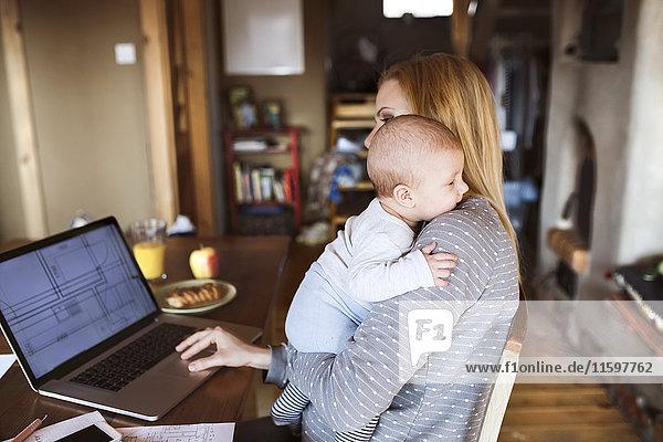 Mutter mit Baby zu Hause mit Laptop