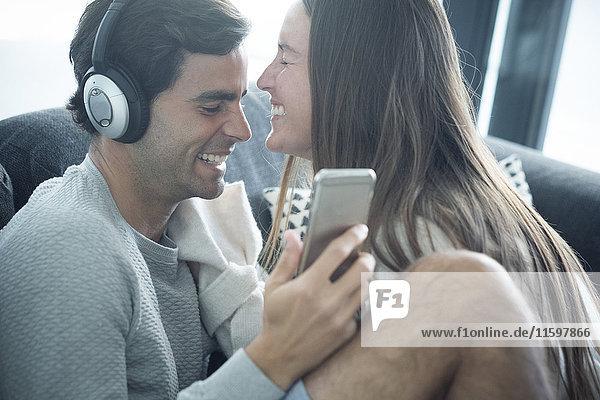 Glückliches junges Paar mit Kopfhörer und Smartphone zu Hause