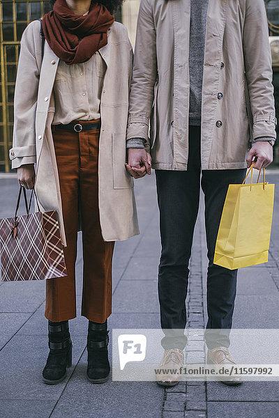 Paar mit Einkaufstaschen  die Händchen halten