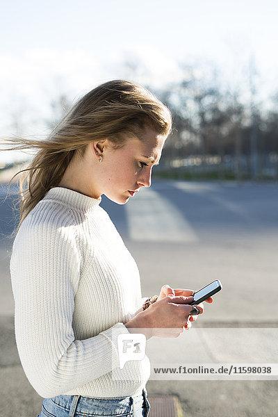 Junge Frau schaut aufs Handy