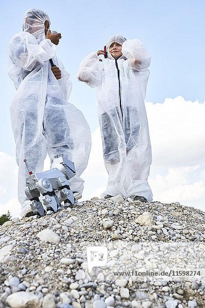Zwei Jungen mit Roboter auf einem Hügel verkleidet als Raumfahrer bei der Mondlandung