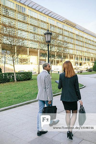 Ein junger Geschäftsmann und eine junge Frau  die in der Stadt spazieren gehen.