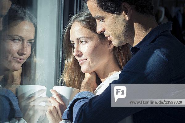 Lächelndes junges Paar schaut aus dem Fenster