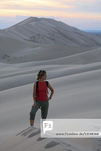 Frau steht auf Sanddünen in der Wüste