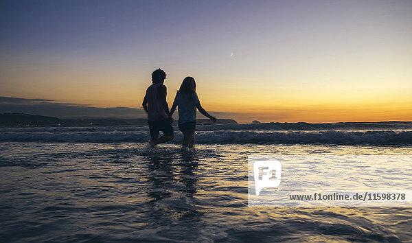 Ein junges Paar  das in der Abenddämmerung im Meer spazieren geht.