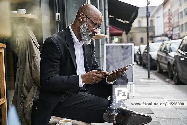 Reife Geschäftsleute sitzen im Cafe mit digitalem Tablett