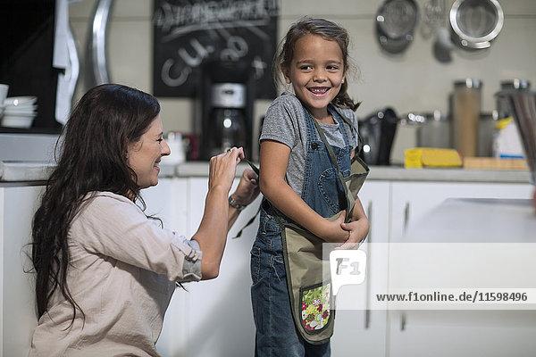 Mutterbindeschürze für Tochter in der Küche