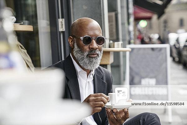 Erwachsener Geschäftsmann trinkt Kaffee im Straßencafé