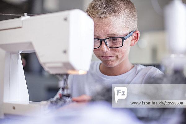 Brillenträger bei der Arbeit an der Nähmaschine