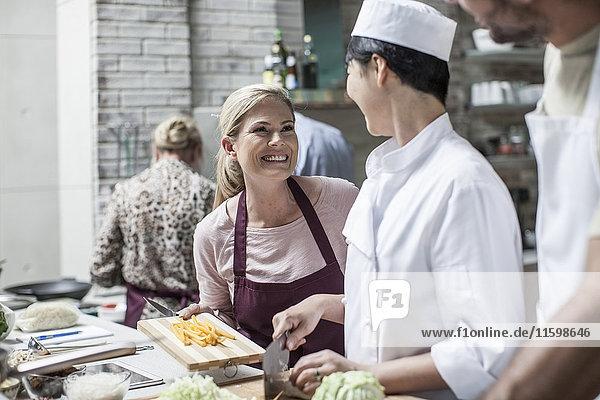 Studentin in der Kochklasse lächelt die Köchin an.