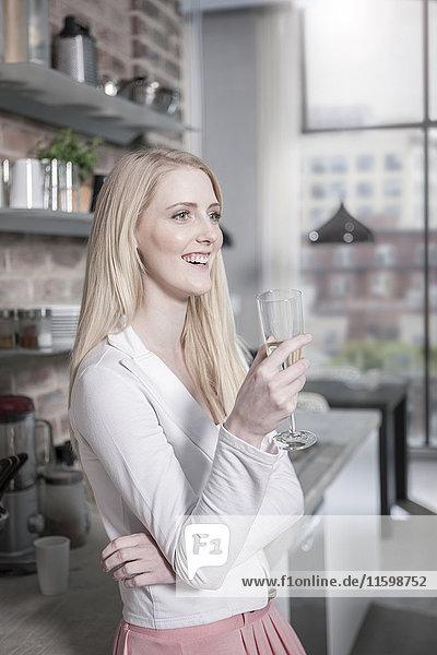 Lächelnde junge Frau trinkt Champagner in der offenen Küche