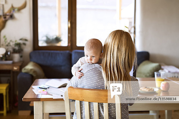 Mother with baby at home sitting at table
