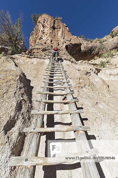 USA  New Mexico  Frijoles Canyon  Bandelier National Monument  Ruinen und rekonstruierte Kiva der Ancestral Pueblo People  Touristen auf der Leiter zum Alcove House.