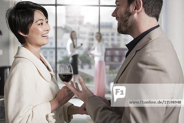 Mann und Frau mit Rotweinglas gesellig in einer Stadtwohnung