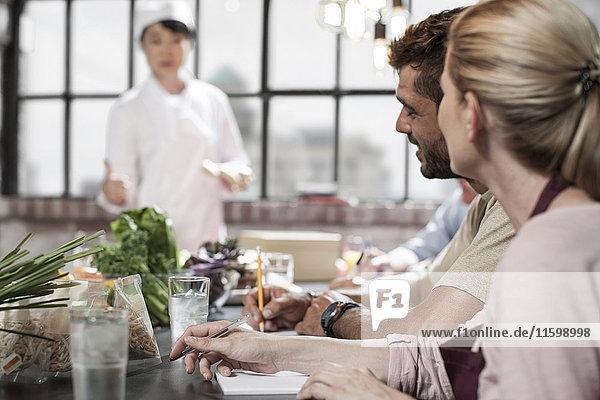Leute  die im Kochkurs Notizen aufschreiben.